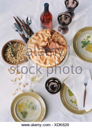 A table laid with dishes of food, nuts, cake, and a bottle of wine. - Stock Photo