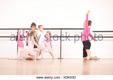 Teacher demonstrating to a group of young ballerinas - Stock Photo