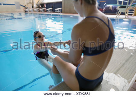 Mother coaching daughter swimming in swimming pool - Stock Photo