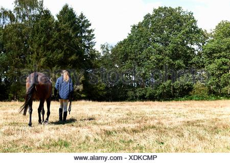 Rear view of girl leading horse in field - Stock Photo