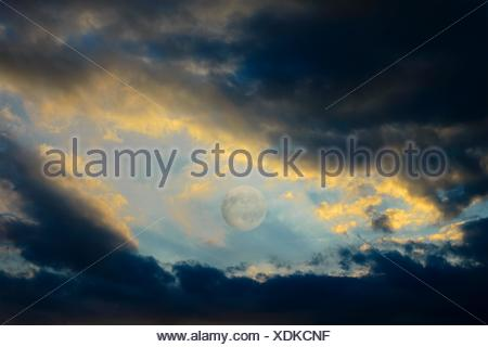 After a violent thunderstorm, between dark clouds still full of rain, backlit by sunset, there is the full moon. - Stock Photo