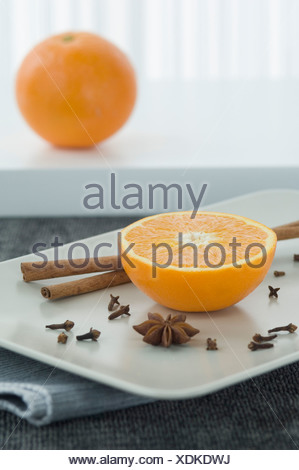 Whole and half orange with cinnamon sticks and star anise on plate, close up - Stock Photo