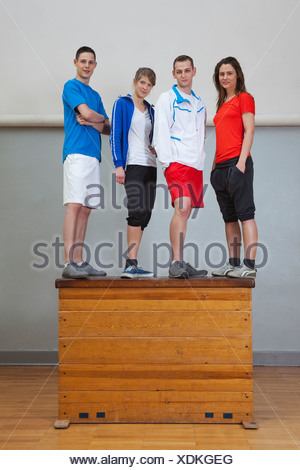 Germany, Berlin, Young men and women standing on vaulting horse - Stock Photo