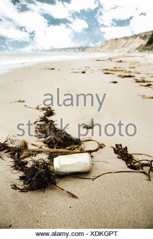 Discarded can on a sandy beach - Stock Photo