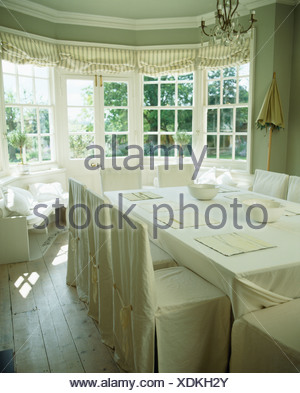 Front Of Bay Window With Striped Blinds White Slip Covers On Chairs In Cream Country Dining Room Linen Cloth Table