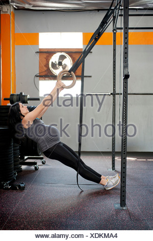 Pregnant young woman pulling gymnastic rings - Stock Photo