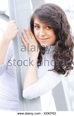 Brunette behind metal beam - Stock Photo