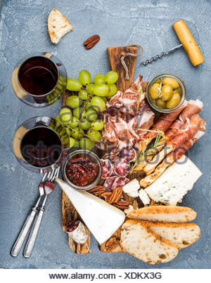 Cheese and meat appetizer selection. Prosciutto di Parma, salami, bread sticks, baguette slices, olives, sun-dried tomatoes, gra - Stock Photo