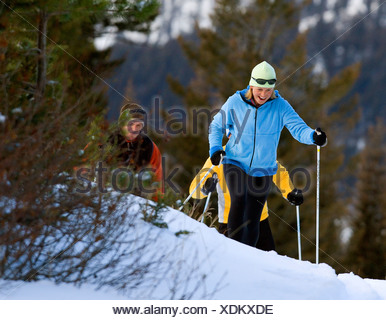 Mid adult woman and a mid adult man skiing - Stock Photo