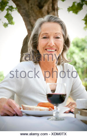 Portrait of smiling woman sitting at laid table in the garden - Stock Photo