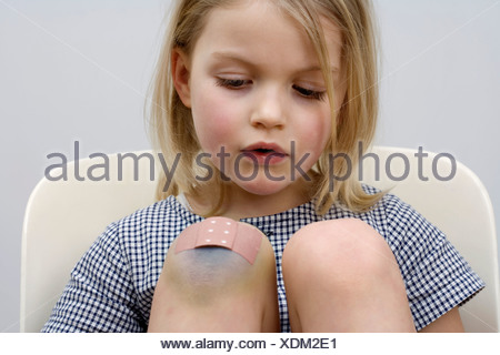 A young girl with a adhesive bandage on her knee - Stock Photo