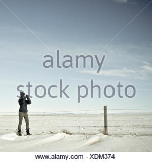 woman looking through binoculars in winter, Wyoming, America, USA - Stock Photo