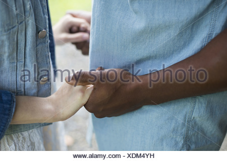 A young man and woman a couple holding hands. - Stock Photo