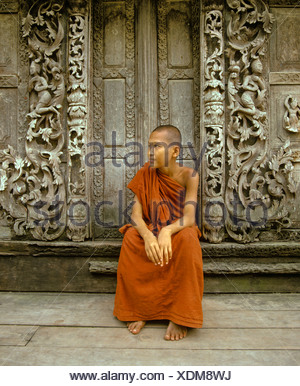 Monk sitting in front of a wooden door with teak carvings, Shwe In Bin Kyaung Monastery, Mandalay, Mandalay Division, Myanmar - Stock Photo
