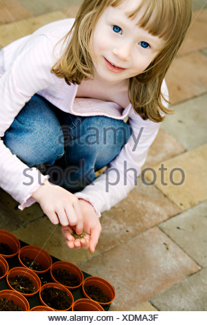 A girl planting flowers in the garden Sweden. - Stock Photo