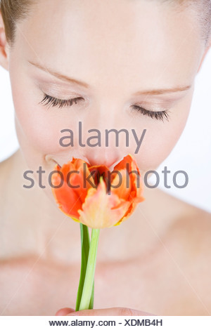 A portrait of a young woman smelling an orange tulip, close-up - Stock Photo