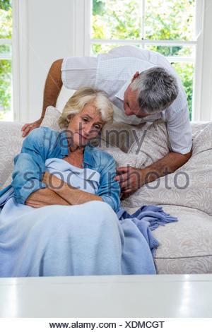 Husband talking to ill senior woman resting on sofa - Stock Photo