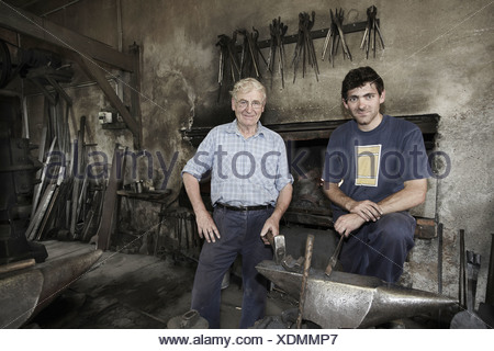 Portrait of blacksmiths in workshop - Stock Photo