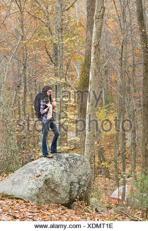 Young woman standing on stone in forest - Stock Photo