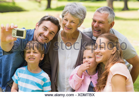 Family photographing themselves with digital camera in park - Stock Photo