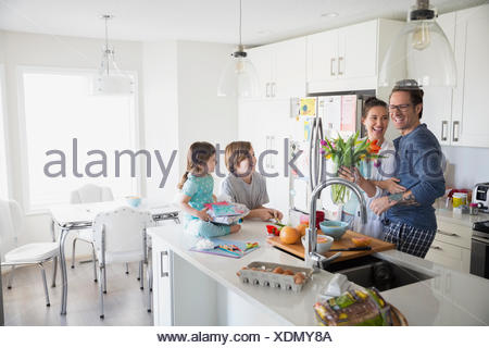 Father and children surprising mother on Mothers Day - Stock Photo