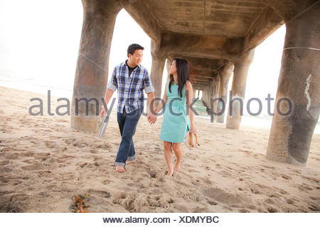 Couple holding hands, walking barefoot  under a pier - Stock Photo