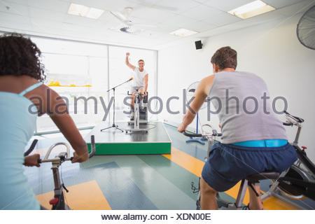 Spin class working out with motivational instructor - Stock Photo