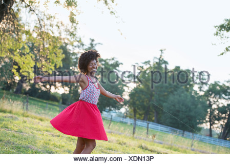 A woman in a red skirt, whirling around in the open air, with her arms outstretched. - Stock Photo