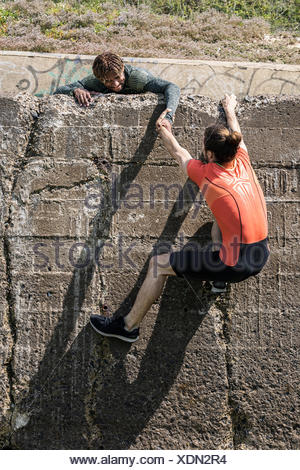 Young male free climber at top of sea wall helping friend climb up - Stock Photo
