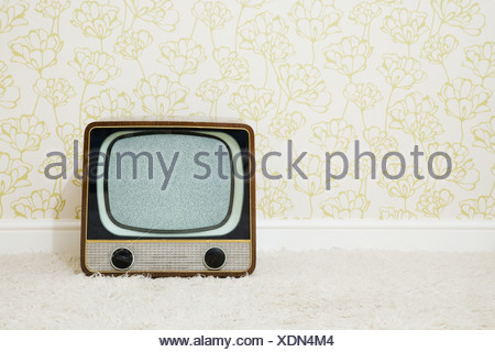 Retro television in room with patterned wallpaper - Stock Photo