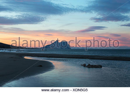 View of The Rock of Gibraltar and La Linea de la Concepcion as seen from the Mediterranean coast at sunset, Cadiz, Andalusia - Stock Photo