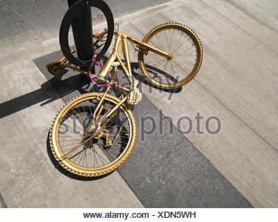 Bicycle painted gold, chained to a post - Stock Photo