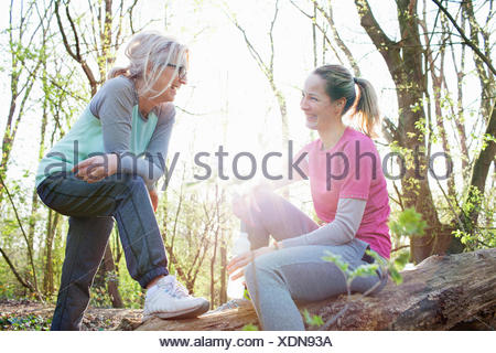 Women in forest sitting on fallen tree face to face smiling - Stock Photo