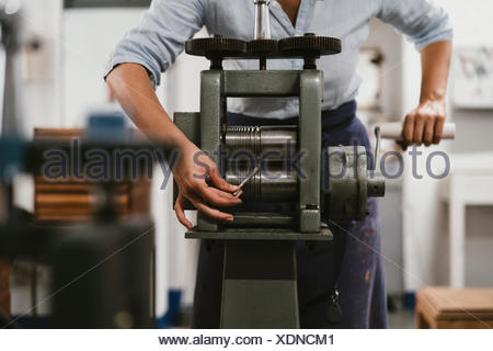 Mid section of female jeweller winding metal rod through machine in jewellery workshop - Stock Photo