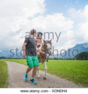Father guiding daughter riding horse, Fuessen, Bavaria, Germany - Stock Photo