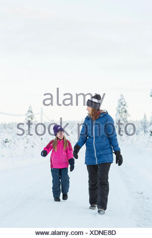 Sweden, Lapland, Gallivare, Girl (4-5) walking with mother along road in winter - Stock Photo