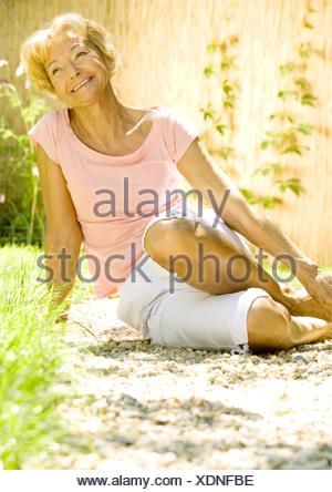 Senior woman sitting on ground outdoors, smiling - Stock Photo