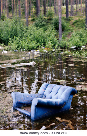 Old armchair in lake in forest - Stock Photo