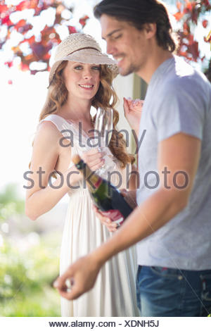 Couple preparing to celebrate with champagne in garden wine bar - Stock Photo