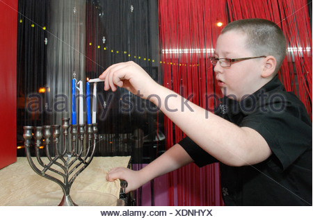 Child lights the Chanukah Menorah - Stock Photo
