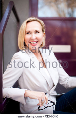Woman sitting on outside steps - Stock Photo