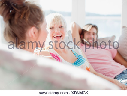 Friends laughing on sofa - Stock Photo