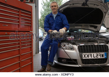 Mechanic with diagnostic computer on car with open bonnet, portrait, low angle view - Stock Photo