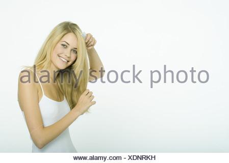 Teenage girl combing hair - Stock Photo