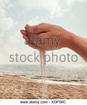 Hands holding and spilling sand with beach in the background - Stock Photo