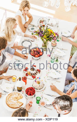 Overhead view of family at birthday party in dining room - Stock Photo