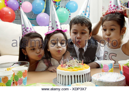 Children celebrating birthday, blowing candles on cake - Stock Photo