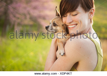 A young woman in a grassy field in spring. Holding a small chihuahua dog in her arms. A pet. - Stock Photo