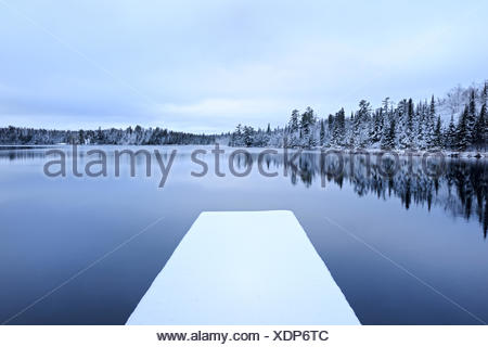 Snow on dock in Lyons Lake in early winter, Whiteshell Provincial Park, Manitoba, Canada - Stock Photo