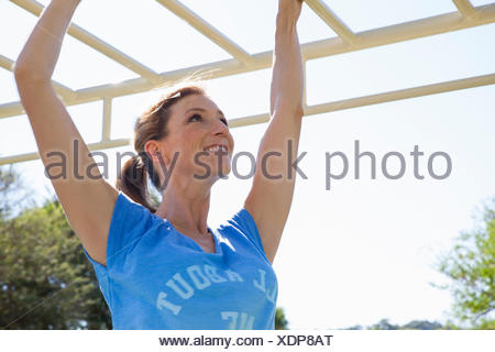 Mid adult woman training on monkey bars in park - Stock Photo